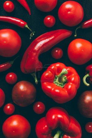Draufsicht auf rote Tomaten, Paprika und Chilischoten auf der Tischplatte