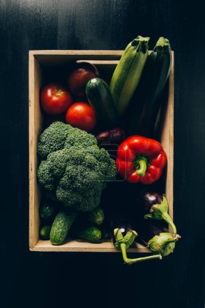 top view of zucchini, broccoli and eggplants in wooden box on dark table