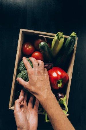 imagen recortada del hombre tomando brócoli de la caja de madera con diferentes verduras