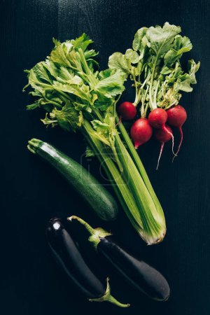 Photo for Top view of celery, radishes and eggplants on grey dark table - Royalty Free Image