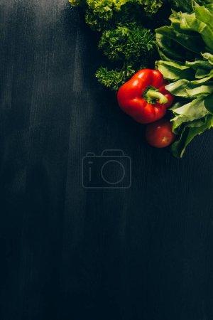 vue de dessus sur gris foncé table de poivrons et salade verte
