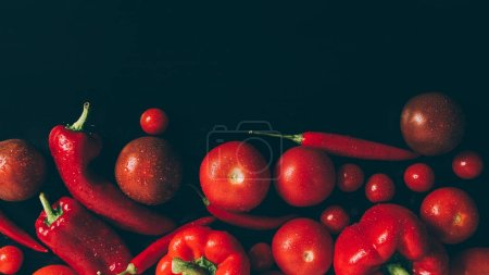 top view of red tomatoes, bell peppers and chili peppers on grey dark table