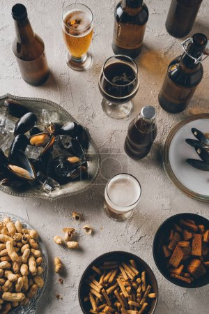 top view of snacks, mussels with ice cubes and cold beer arranged on concrete tabletop