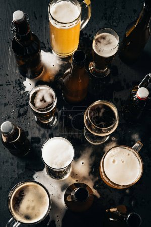 top view of arrangement of bottles and glasses of beer on dark wooden tabletop