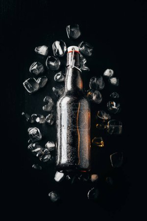 flat lay with glass bottle of beer on ice cubes arranged on dark tabletop