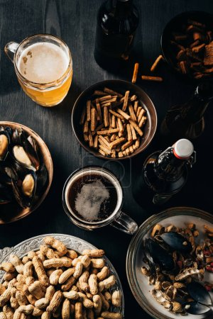 top view of table set with snacks and beer on dark wooden surface