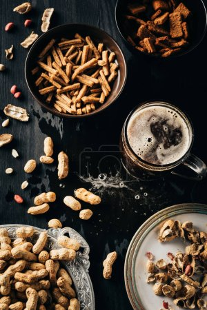 top view of table set with snacks and glass of beer on dark wooden surface