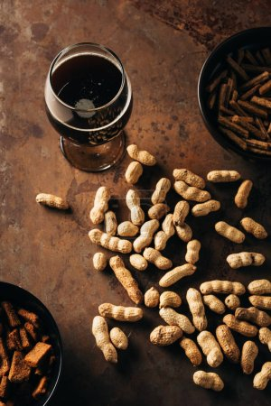 top view of peanuts, baked breads and glass of beer on rust tabletop