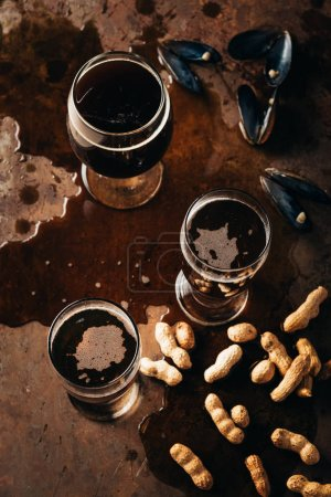 top view of glasses of cold beer, peanuts and mussels shells on rust surface