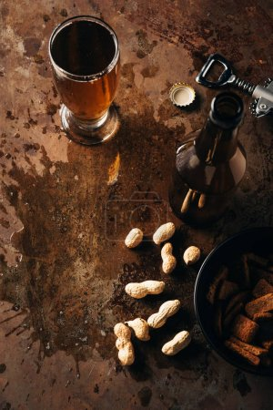 top view of arranged peanuts, baked breads, bottle and glass of beer on rust tabletop