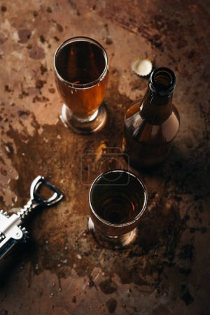 top view of mugs of beer, bottle and bottle opener on rust surface