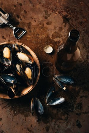 flat lay with opened glass bottle of beer, bottle opener and mussels in bowl on rust surface