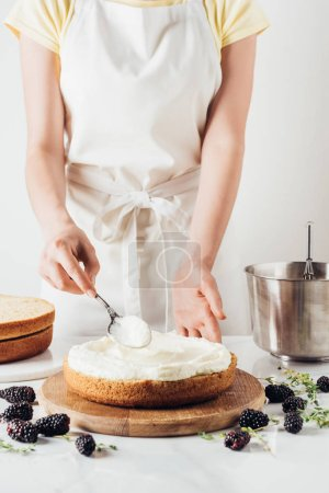 cropped shot of woman in white apron applying cream onto freshly baked cake on white