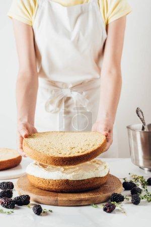 Photo pour Photo recadrée de femme faisant délicieux gâteau blanc en couches - image libre de droit