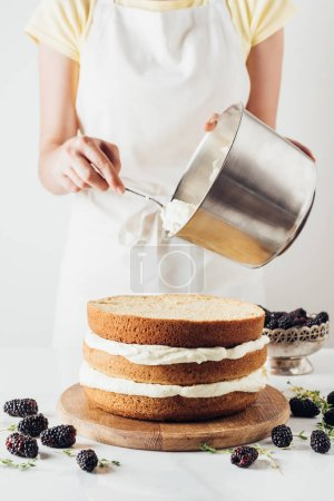 cropped shot of woman pouring cream onto freshly baked cake on white