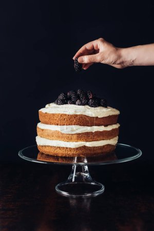 cropped shot of woman decorating tasty blackberry cake on glass stand on black