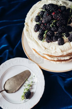 high angle view of freshly baked blackberry cake with plate and cake server o blue cloth