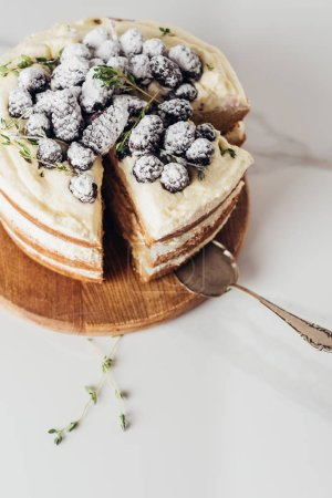 Photo for Close-up shot of tasty sliced blackberry cake on wooden cutting board with cake server - Royalty Free Image