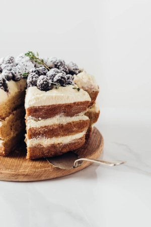 close-up shot of delicious sliced blackberry cake on wooden cutting board with cake server