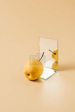 Photo pour Délicieuse poire jaune réfléchissant dans deux miroirs sur table beige - image libre de droit