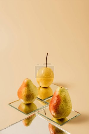 yellow whole pears reflecting in mirrors on beige table