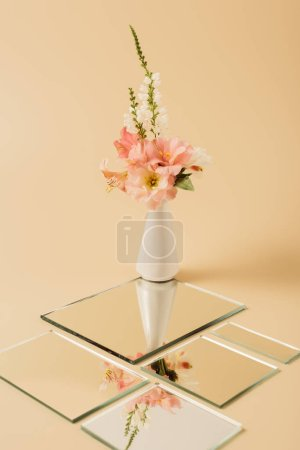lily flowers in vase reflecting in mirrors on beige table