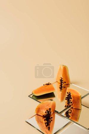 Photo pour Morceaux de papaye reflétant dans les miroirs sur table beige - image libre de droit