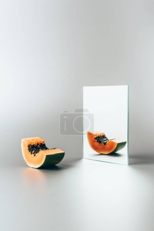 exotic papaya reflecting in mirror on white table