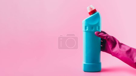 Photo for Cropped image of female cleaner in rubber glove holding cleaning fluid, pink background - Royalty Free Image