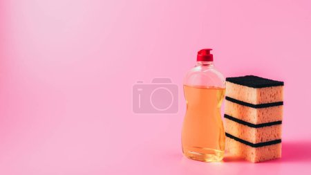 close up view of dishwashing liquid and stack of washing sponges, pink background