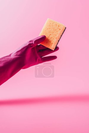 Photo for Partial view of female cleaner in rubber glove holding washing sponge, pink background - Royalty Free Image