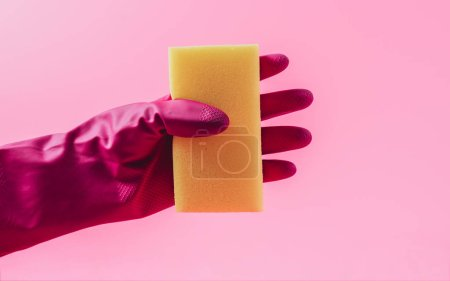 Photo for Cropped image of female cleaner in rubber glove holding washing sponge, pink background - Royalty Free Image