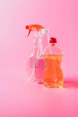 close up view of dishwashing liquid and cleaning fluids, pink background