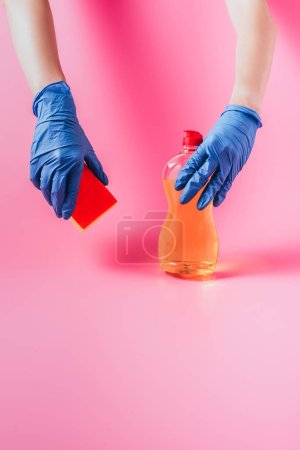 cropped image of woman in rubber glove holding washing sponge and dishwashing liquid, pink background