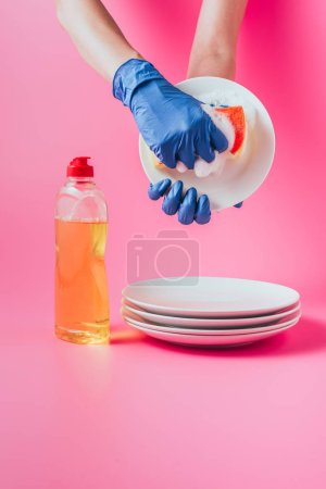 cropped image of female cleaner in rubber glove washing plate, pink background