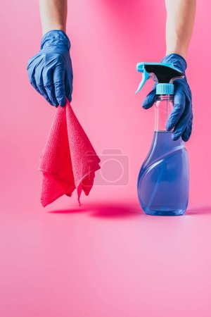 Photo for Cropped image of female cleaner holding cleaning fluid and rag, pink background - Royalty Free Image