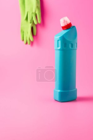 close up view of cleaning fluid and rubber gloves behind, pink background