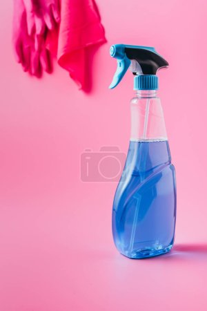 close up view of cleaning fluid and rag with rubber gloves behind, pink background