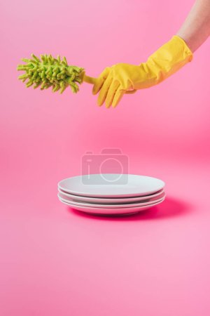 cropped image of woman in rubber glove holding dish microfiber brush over stack of white plates, pink background
