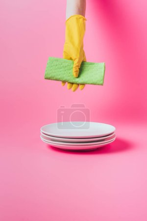 Photo for Cropped image of woman holding cleaning napkin over stack of clean white plates, pink background - Royalty Free Image
