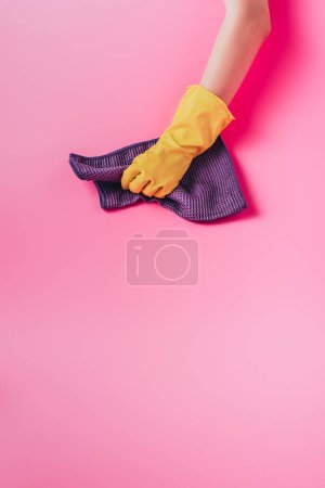 Photo for Cropped image of female cleaner wiping dust by rag, pink background - Royalty Free Image