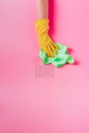 Photo for Partial view of female cleaner wiping dust by rag, pink background - Royalty Free Image