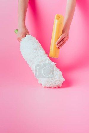 Photo pour Image recadrée de femme tenant nettoyant spray peut et plumeau, rose fond blanc - image libre de droit