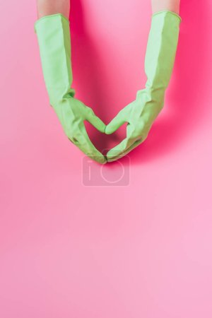 cropped image of female cleaner in rubber gloves making heart symbol by hands, pink background
