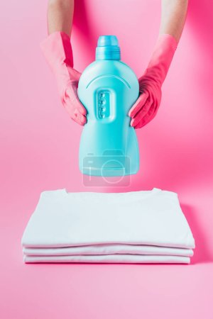 Photo for Cropped image of female cleaner in rubber gloves holding laundry liquid over stack of clean white t-shirts, pink background - Royalty Free Image