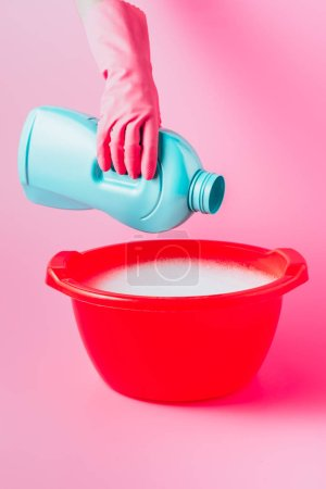 Photo for Partial view of female cleaner pouring laundry liquid in plastic basin with foam, pink background - Royalty Free Image