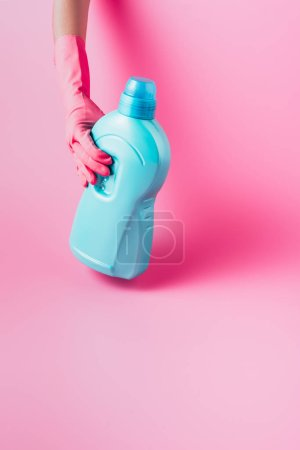 Photo for Cropped image of woman in rubber glove holding laundry liquid, pink background - Royalty Free Image