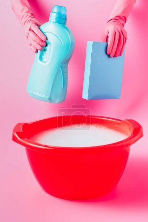 Photo for Cropped image of female cleaner in rubber gloves holding laundry liquid and washing powder over plastic basin with foam, pink background - Royalty Free Image
