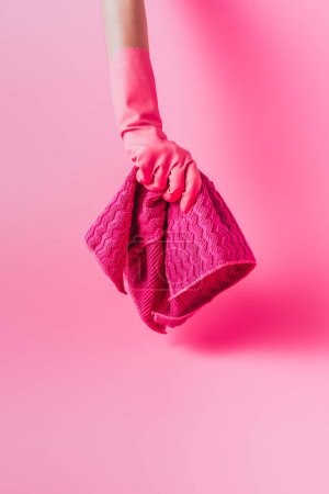 partial view of female cleaner in rubber glove holding rag, pink background