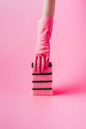 Photo for Cropped image of woman in rubber glove holding stack of washing sponges, pink background - Royalty Free Image